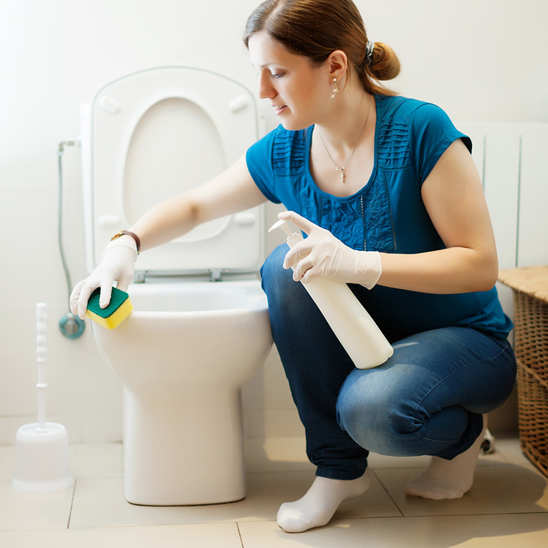 happy homes team member cleaning a bathroom