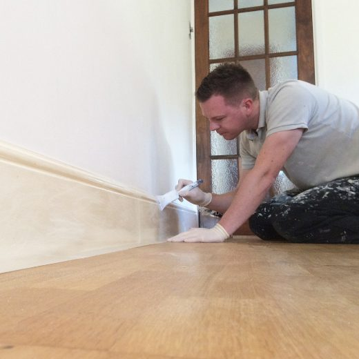 Happy Homes team member painting a skirting board